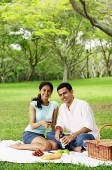 Couple in park, having a picnic, looking at camera - Asia Images Group