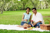 Couple having a picnic, looking at camera, portrait - Asia Images Group