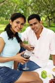 Couple holding wine glasses, looking at camera, portrait - Asia Images Group