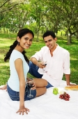 Couple holding wine glasses, sitting on picnic blanket - Asia Images Group