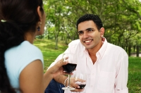 Couple holding wine glasses in park, over the shoulder view - Asia Images Group