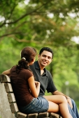 Couple sitting on bench, talking - Asia Images Group