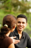 Man facing woman, smiling, over the shoulder view - Asia Images Group