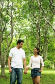 Couple walking in park, holding hands, looking at each other - Asia Images Group