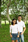 Couple standing in park, looking at camera - Asia Images Group