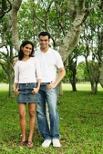 Couple standing in park, looking at camera, portrait - Asia Images Group