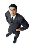 Businessman, hands on waist, looking up at camera - Asia Images Group