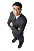 Businessman, arms crossed, looking up at camera - Asia Images Group