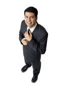 Businessman, adjusting tie, looking at camera - Asia Images Group