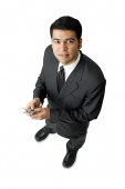 Businessman, holding mobile phone, looking at camera - Asia Images Group
