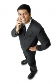 Businessman, using mobile phone, looking at camera, hand on hip - Asia Images Group