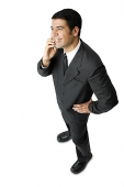 Businessman, using mobile phone, hand on hip - Asia Images Group