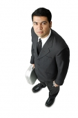 Businessman, holding mobile phone and briefcase, looking up at camera - Asia Images Group