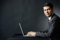 Businessman using laptop, looking at camera - Asia Images Group