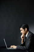 Businessman in front of laptop, hand on chin - Asia Images Group