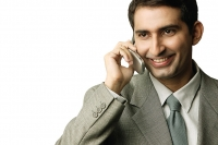 Businessman using mobile phone, smiling - Asia Images Group
