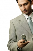 Businessman holding mobile phone, looking down - Asia Images Group