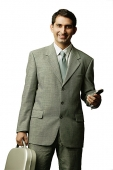 Businessman holding mobile phone and briefcase, looking at camera - Asia Images Group