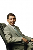 Businessman sitting on chair, smiling at camera - Asia Images Group