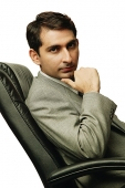 Businessman sitting on chair, hand on chin, looking at camera - Asia Images Group