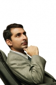 Businessman sitting on chair, hand on chin, away - Asia Images Group