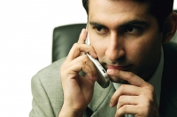 Businessman using mobile phone, looking away - Asia Images Group