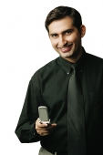 Executive holding mobile phone, smiling at camera - Asia Images Group