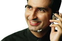 Executive using headset, smiling, looking away - Asia Images Group