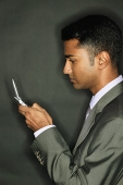 Businessman using mobile phone, side view - Asia Images Group