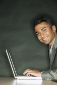 Businessman using laptop, smiling at camera - Asia Images Group