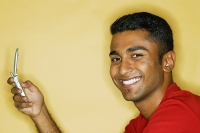Man holding mobile phone, smiling at camera - Asia Images Group