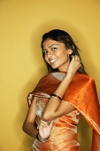 Woman in Indian clothing, smiling at camera, hand on neck - Asia Images Group