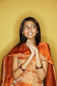 Woman in Indian clothing, hands clasped, smiling - Asia Images Group
