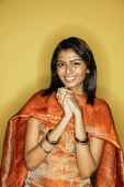 Woman in Indian clothing, hands clasped, smiling at camera - Asia Images Group