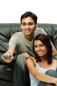 Couple sitting and facing forward, man holding remote control - Asia Images Group
