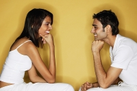 Couple sitting face to face, hands on chin - Asia Images Group
