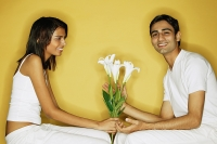 Couple sitting face to face, woman holding flowers, man looking at camera - Asia Images Group