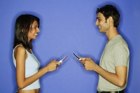 Couple face to face, holding mobile phones - Asia Images Group