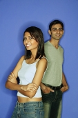 Woman standing in front of man, arms crossed, man behind with hands in pocket - Asia Images Group