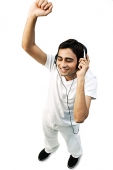 Young man listening to headphones, eyes closed, arms raised - Asia Images Group
