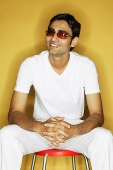 Young man sitting on stool, wearing sunglasses - Asia Images Group