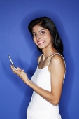 Woman looking at camera, holding mobile phone - Asia Images Group
