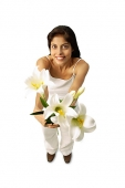 Woman standing, holding flowers, looking at camera - Asia Images Group