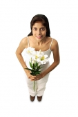 Woman standing with flowers, looking at camera - Asia Images Group