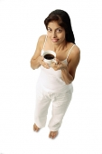 Woman holding cup of coffee, looking up at camera - Asia Images Group