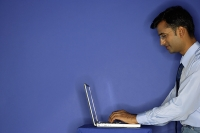 Man using laptop, side view - Asia Images Group