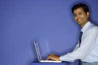 Man using laptop, smiling at camera - Asia Images Group