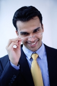 Businessman adjusting glasses, smiling at camera - Asia Images Group