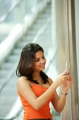 Woman standing and holding mobile phone, smiling - Asia Images Group