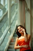 Woman leaning in glass wall using mobile phone, smiling - Asia Images Group